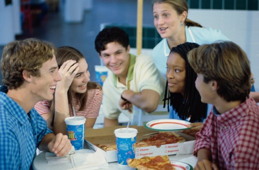 Group of teenagers eating pizza in a restaurant : Stock Photo