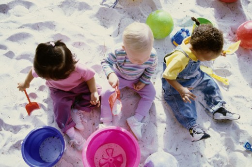 High angle view of a girl and two boys playing in the sand : Stock Photo