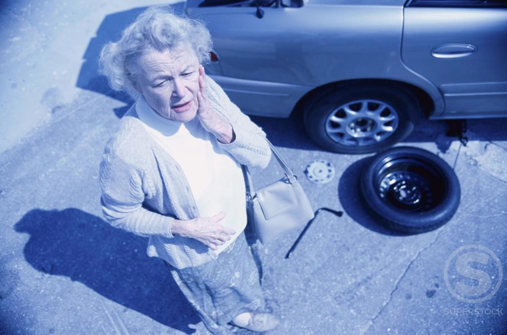 Stock Photo: 1099R-5166 Senior woman standing beside a broken down car