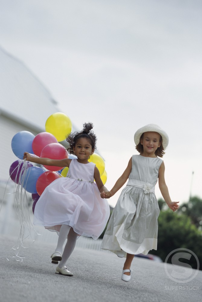 Stock Photo: 1099R-5366 Two girls running together holding hands