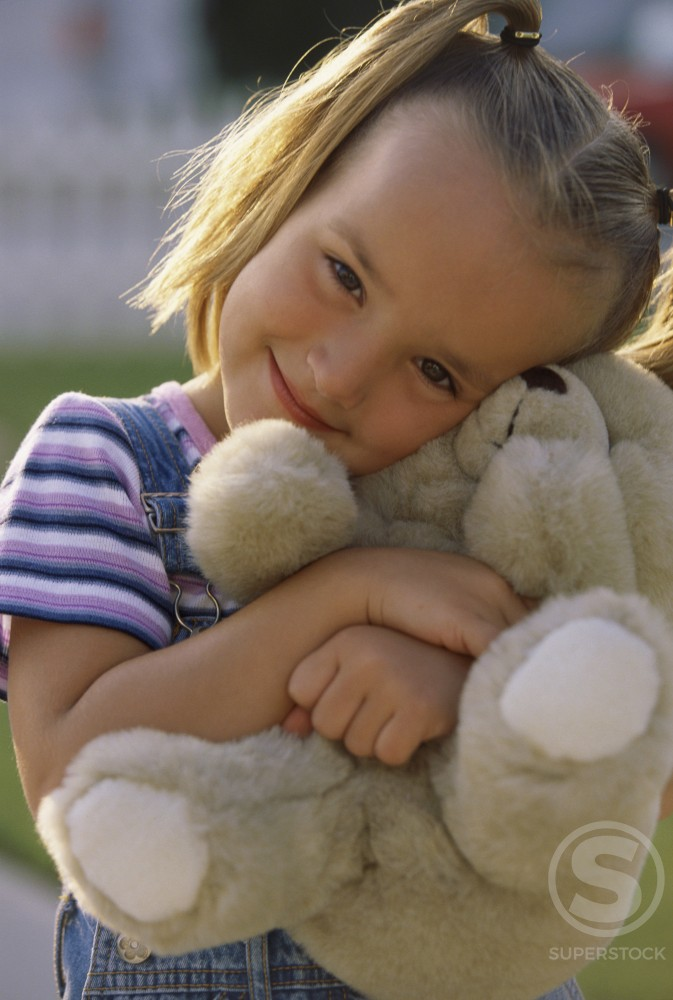 Stock Photo: 1099R-5379 Portrait of a girl holding a teddy bear smiling