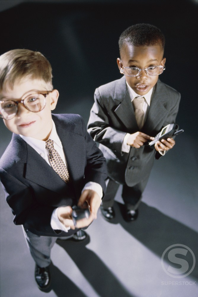 High angle view of two young boys dressed as businessmen operating mobile phones : Stock Photo