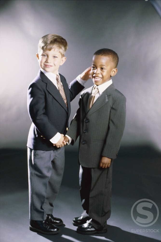 Portrait of two young boys dressed as businessmen shaking hands : Stock Photo