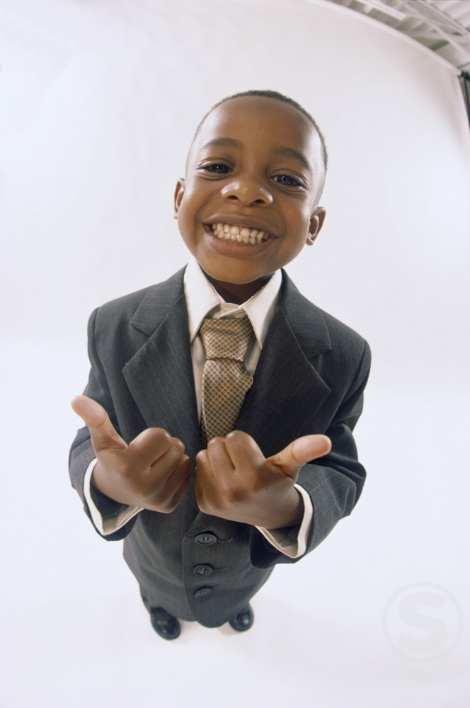Portrait of a young boy dressed as a businessman gesturing thumbs up smiling : Stock Photo