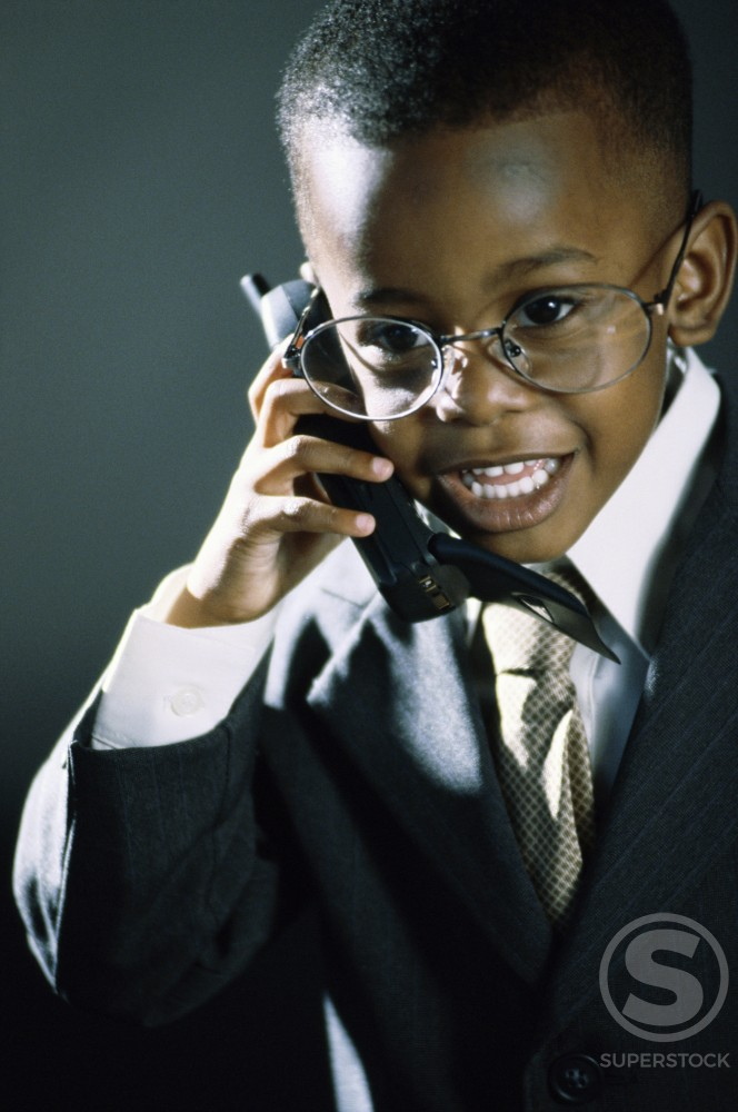 Stock Photo: 1099R-5537A Young boy dressed as a businessman talking on a mobile phone