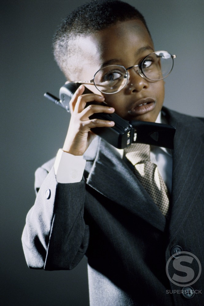 Young boy dressed as a businessman talking on a mobile phone : Stock Photo