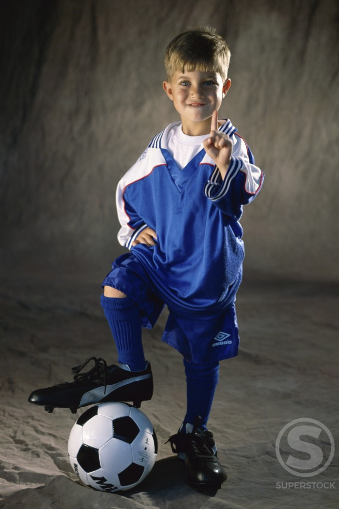 Portrait of a boy standing with his foot on a soccer ball : Stock Photo