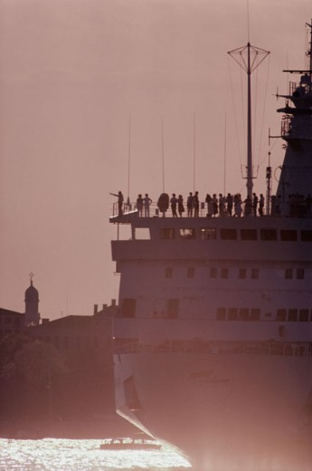 Silhouette of a group of tourists standing on a cruise ship : Stock Photo