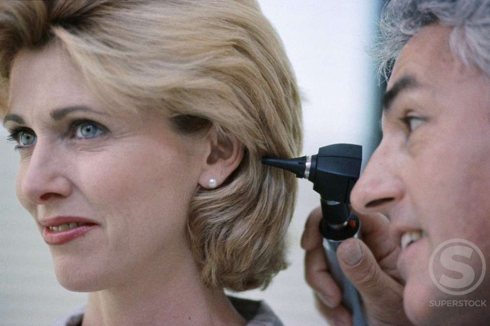 Stock Photo: 1118-107 Close-up of a male doctor examining a female patient's ear