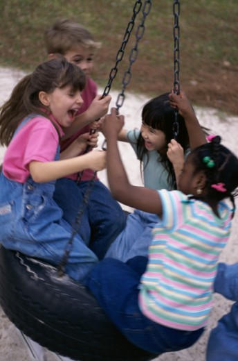 Stock Photo: 1118-109 Group of children on a tire swing