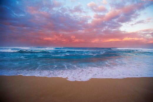Waves breaking on the beach at dusk : Stock Photo