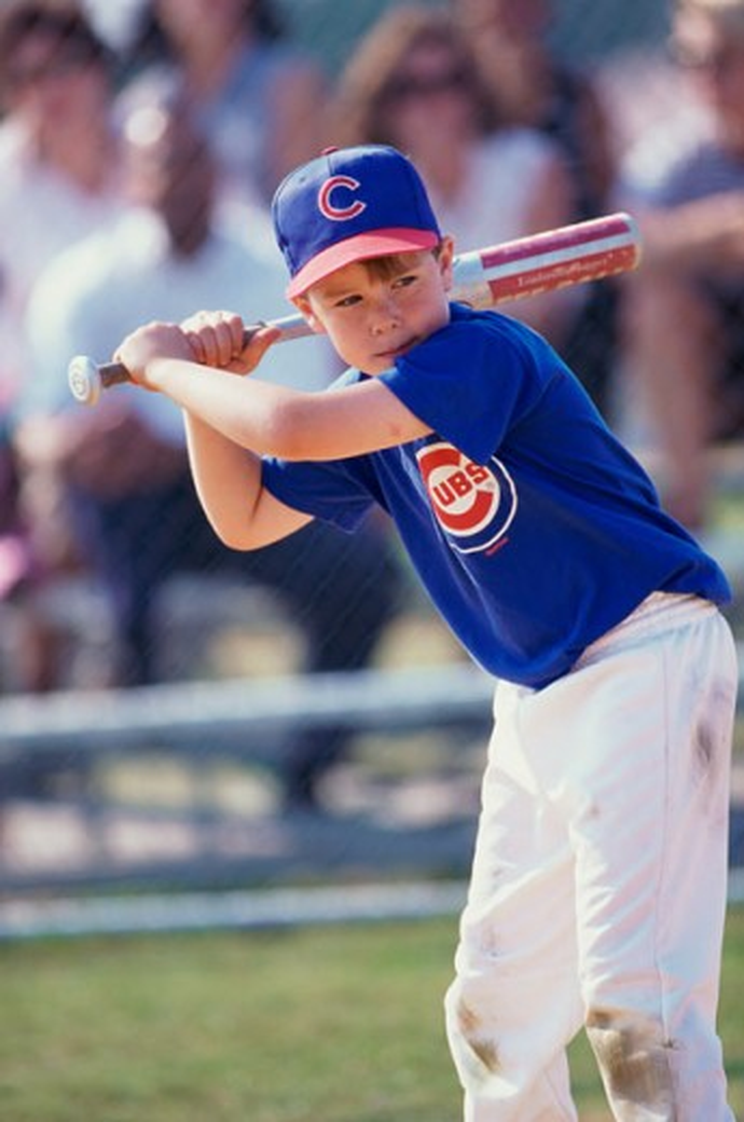 Boy swinging a baseball bat on a field : Stock Photo