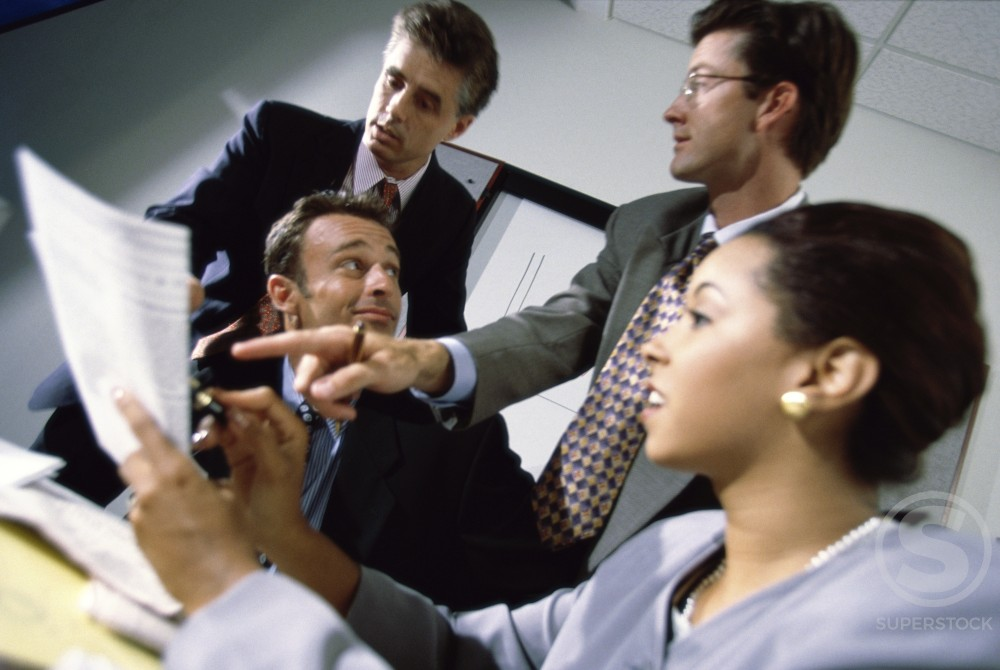Businesswoman with three businessmen in an office : Stock Photo