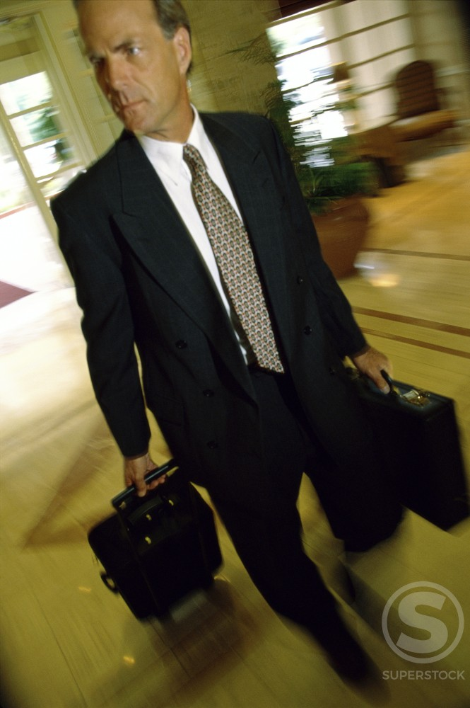 Stock Photo: 1128-576 Businessman walking with luggage in a hotel
