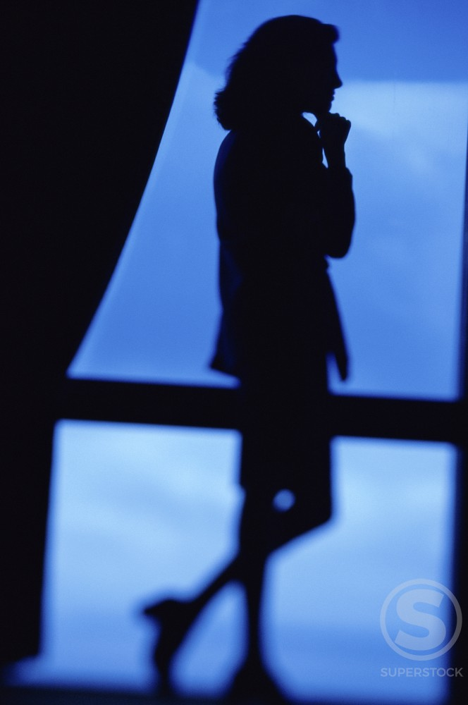 Silhouette of a businesswoman looking out of a window : Stock Photo