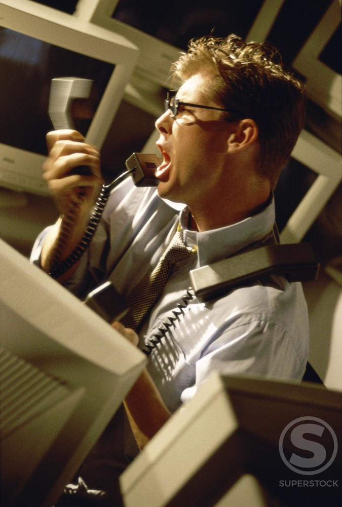 Side profile of a businessman shouting on the telephone : Stock Photo