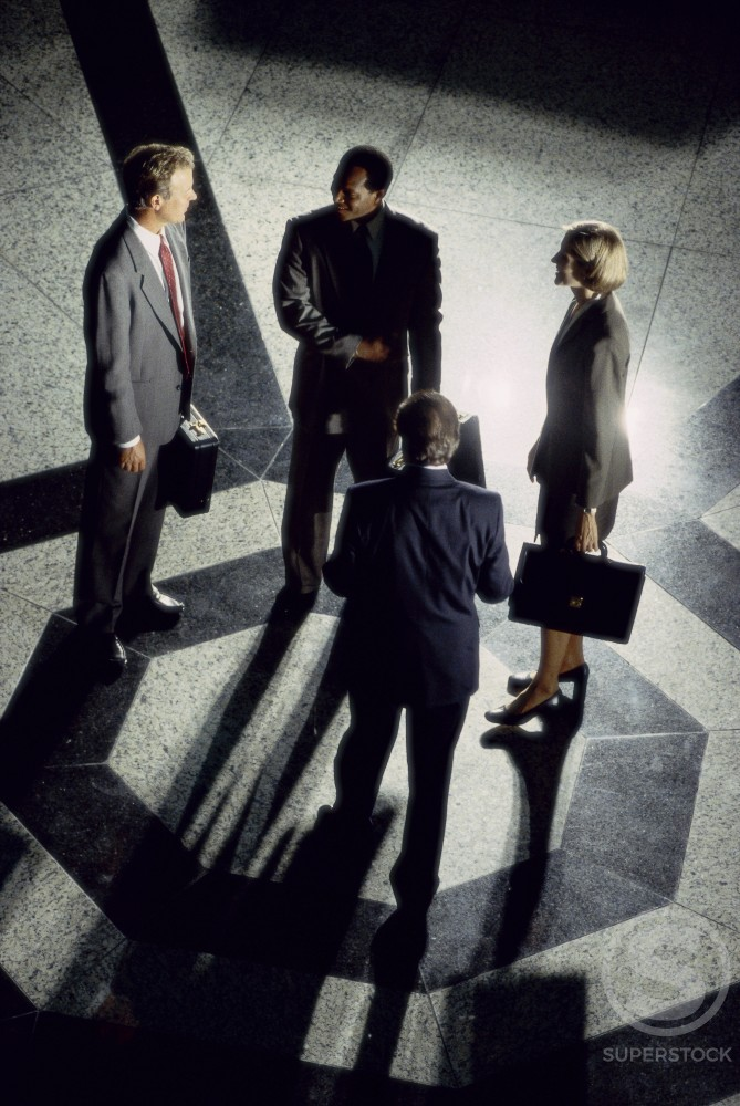 High angle view of business executives standing together talking : Stock Photo
