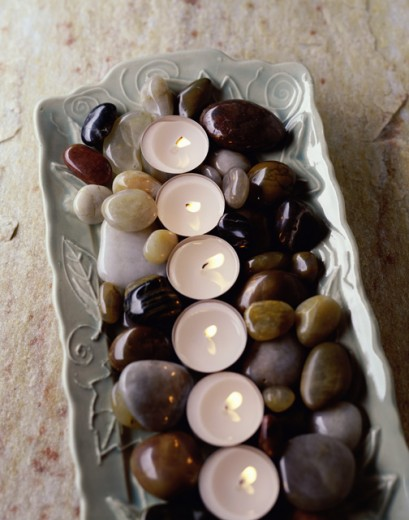 Stock Photo: 1163-366 High angle view of burning candles with pebbles on a tray