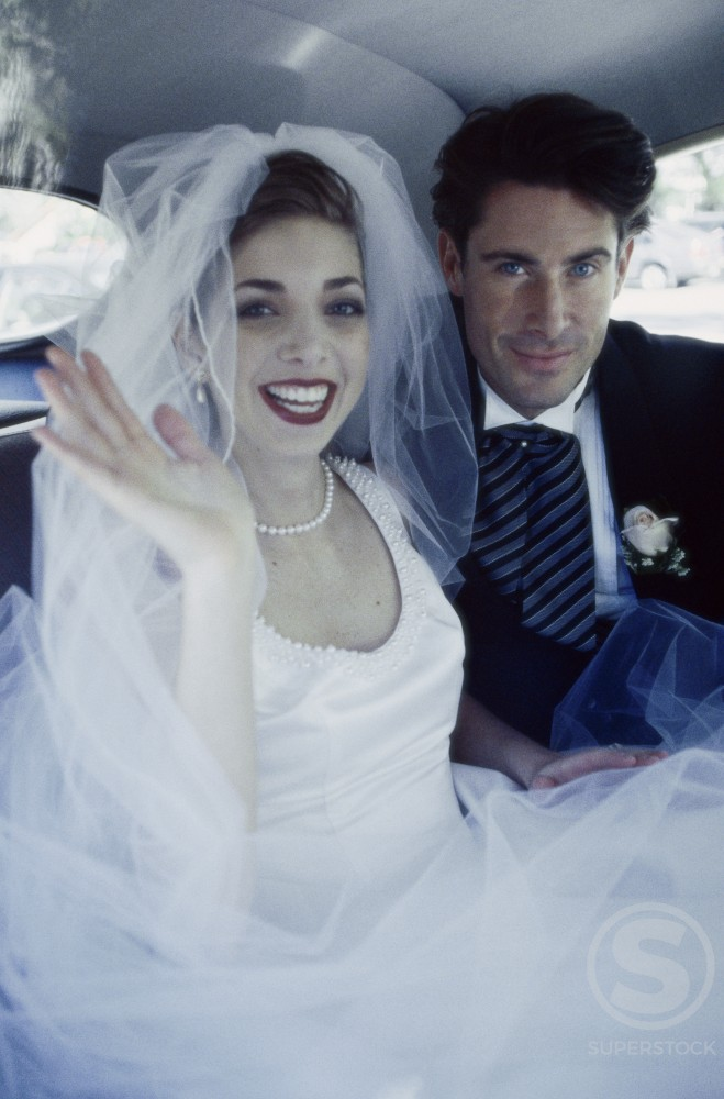 Portrait of a newlywed couple sitting in a car : Stock Photo