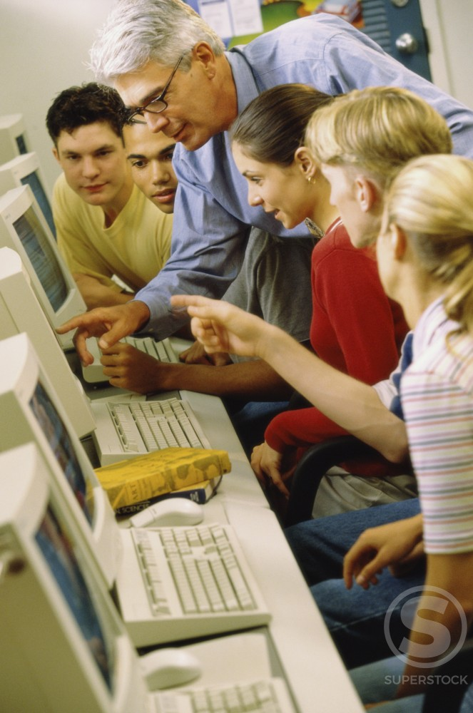 Male teacher and his students in front of computers : Stock Photo
