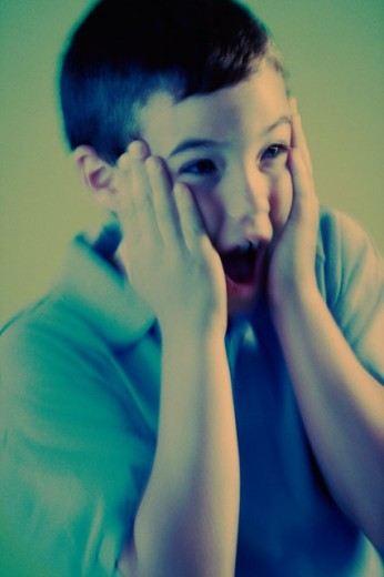 Close-up of a boy shouting in surprise : Stock Photo