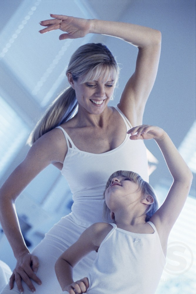 Woman and child exercising together : Stock Photo