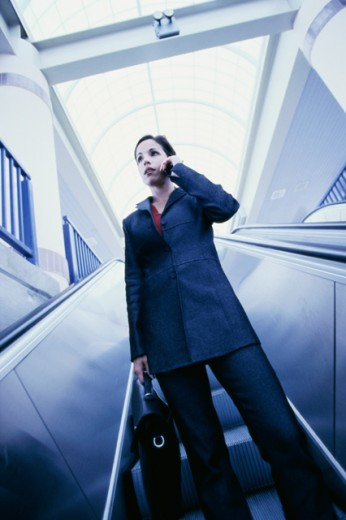 Stock Photo: 1166-4962A Low angle view of a businesswoman standing on an escalator talking on a mobile phone
