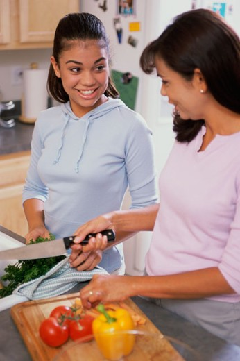 Stock Photo: 1166-4984D Teenage girl with her mother cooking in a kitchen
