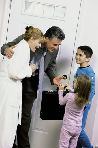 Stock Photo: 1166-5137A Son and daughter greeting their father at the front door