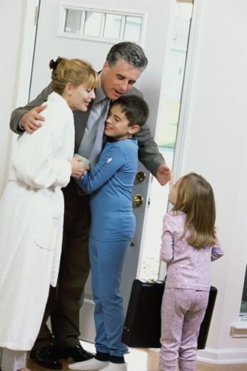 Stock Photo: 1166-5138 Son and daughter greeting their father at the front door