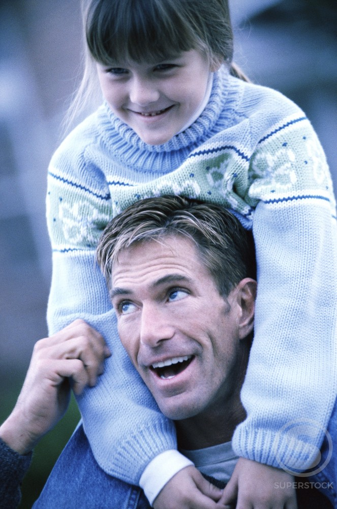 Daughter sitting on her father's shoulders : Stock Photo