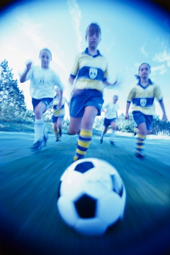 Stock Photo: 1166-742A Five teenage girls chasing a soccer ball