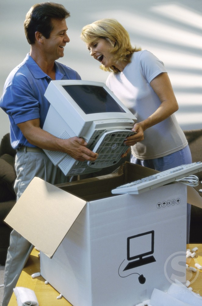 Stock Photo: 1166-917 Young couple unpacking a computer monitor