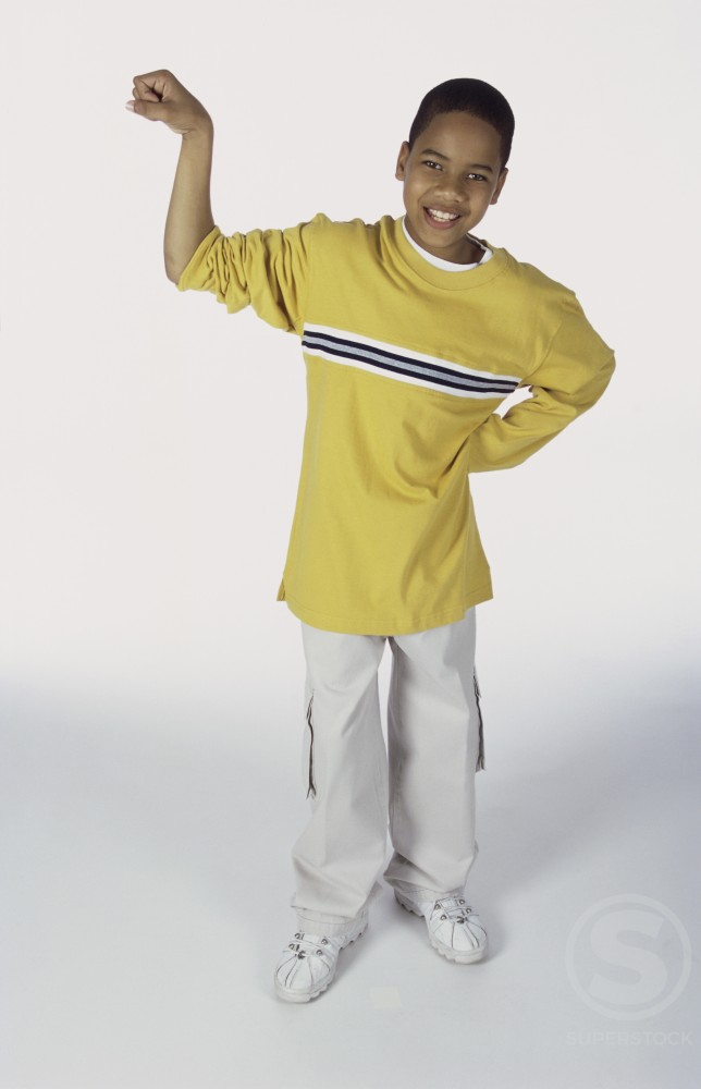 Portrait of a boy standing with his arm raised : Stock Photo
