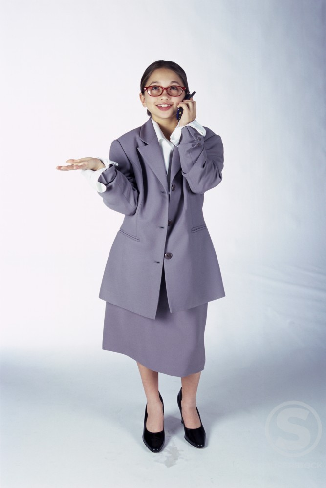 Stock Photo: 1166R-4143A Portrait of a young girl dressed as a businesswoman talking on a mobile phone