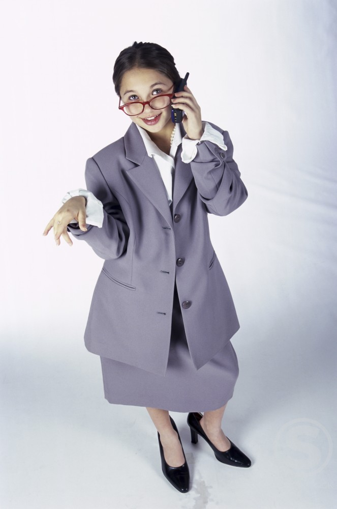 Portrait of a young girl dressed as a businesswoman talking on a mobile phone : Stock Photo
