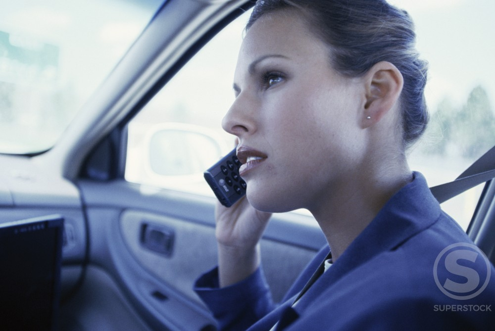 Stock Photo: 1166R-4211 Side profile of a businesswoman talking on a mobile phone in a car