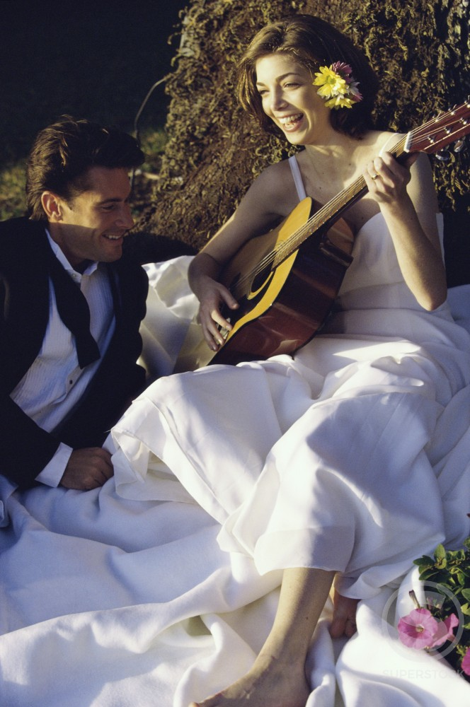 Bride and groom sitting together playing a guitar : Stock Photo