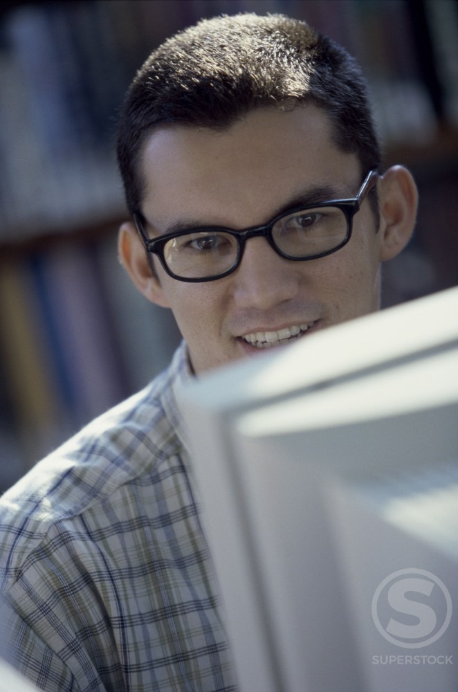 Stock Photo: 1166R-4466 Portrait of a young man sitting in front of a computer monitor