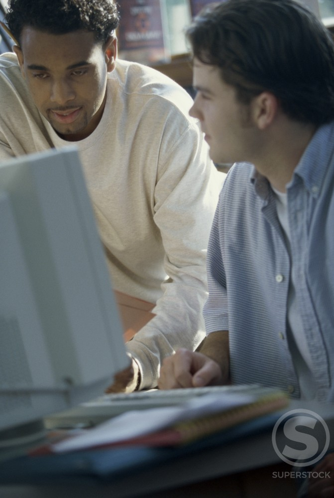 Two young men looking at a computer monitor : Stock Photo