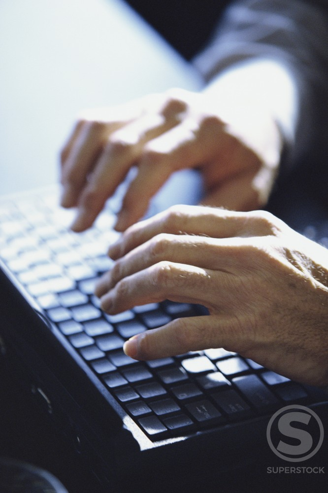 High angle view of a person's hand operating a computer keyboard : Stock Photo