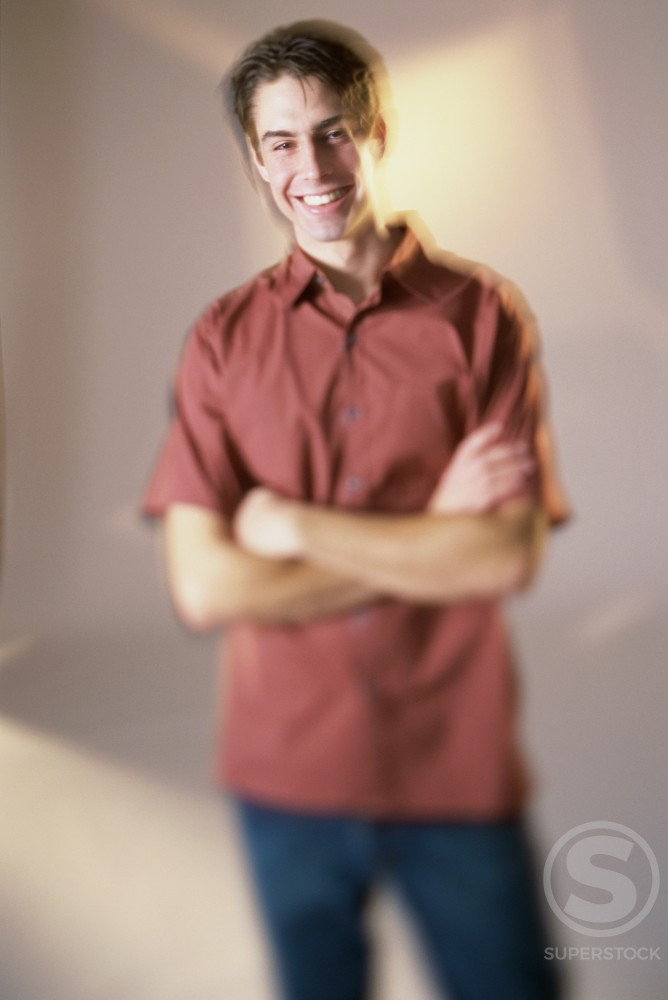Stock Photo: 1166R-4558 Portrait of a young man standing with arms folded