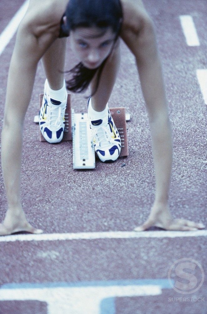 Young female runner at the starting position : Stock Photo