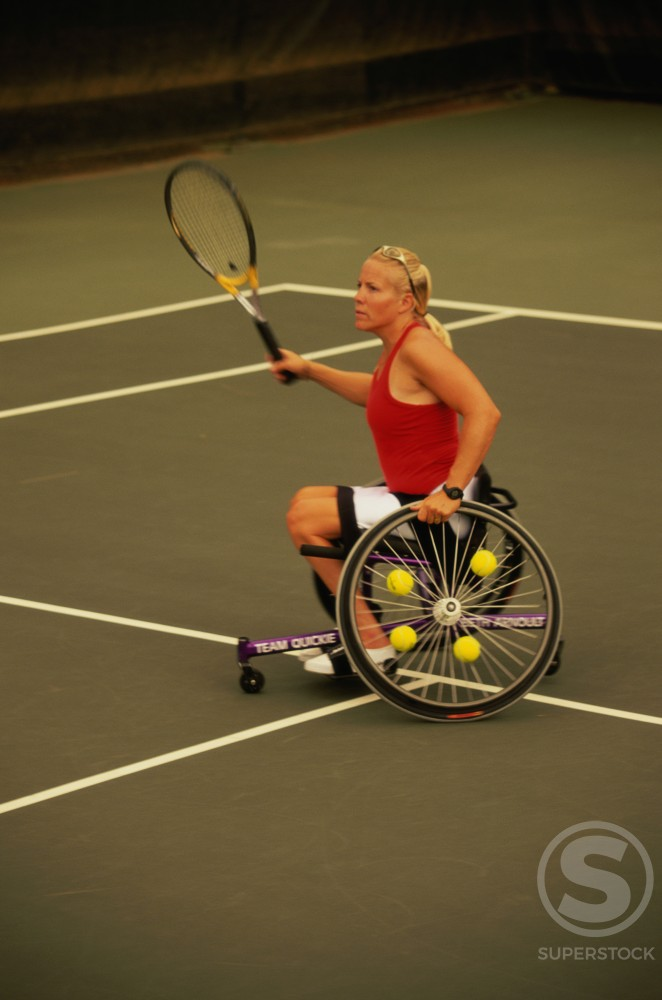 Stock Photo: 1176-298 Side profile of a young woman in a wheel chair playing tennis