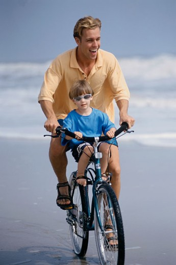 Stock Photo: 1177-185 Mid adult man and his son riding a bicycle on the beach