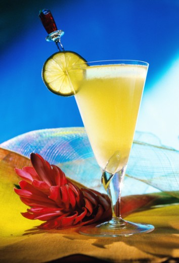 Close-up of a cocktail with a flower beside it : Stock Photo