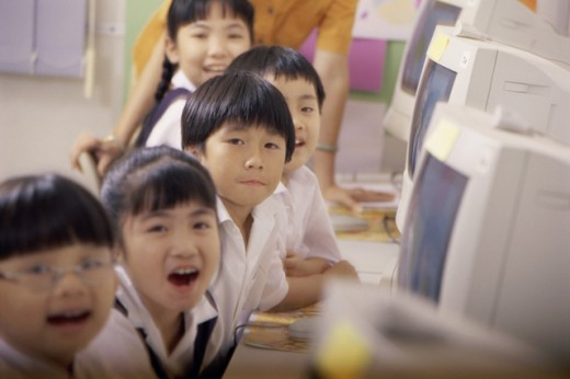 Portrait of children sitting in front of computers : Stock Photo