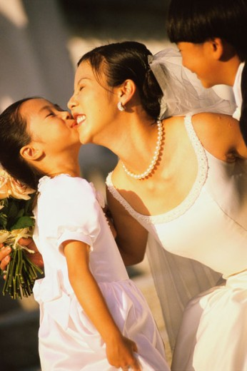 Stock Photo: 1188-1099 Bridesmaid kissing the bride with a ring bearer standing beside her
