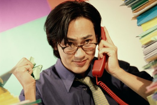 Stock Photo: 1188-227 Close-up of a young businessman using a landline telephone in the office