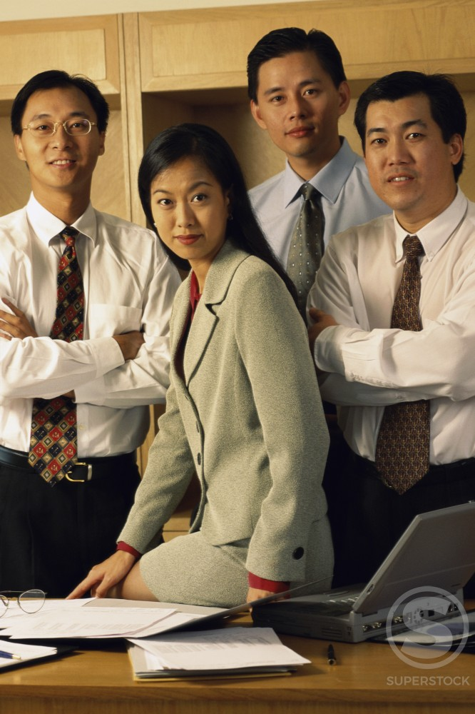 Portrait of three businessmen and a businesswoman smiling in an office : Stock Photo